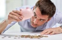 Finanzkrise, Mann mit Sparschwein kaputt, Geld auf Tisch