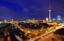 Beleuchtete Straßen und Wohnungen in Berlin bei Dämmerung.